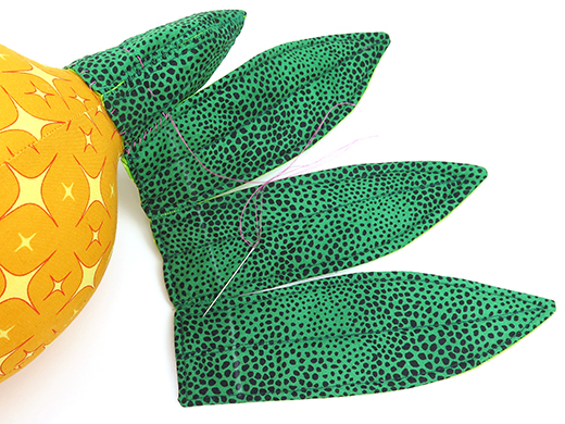 sew large leaves to pineapple cushion